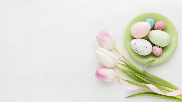 Vista dall'alto di uova di pasqua colorate sul piatto con tulipani
