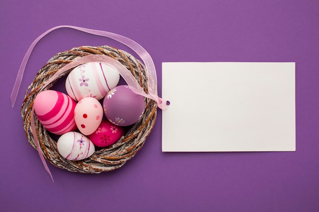 Top view of colorful easter eggs with basket and paper