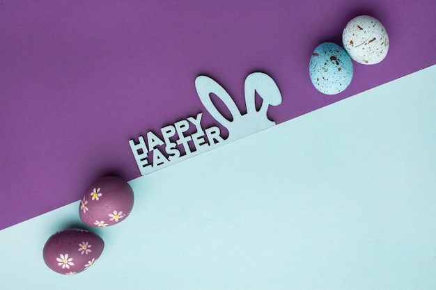 Top view of colorful easter eggs with bunny ears and greeting