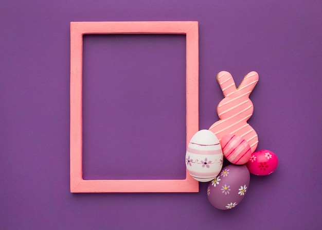 Top view of colorful easter eggs with bunny and frame