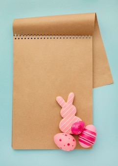 Top view of colorful easter eggs with notebook and bunny
