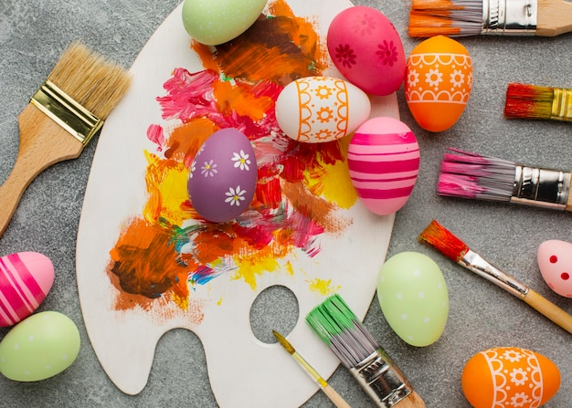 Top view of colorful easter eggs with paint brushes and palette