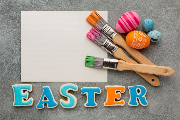 Top view of colorful easter eggs with paint brushes and paper
