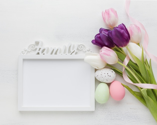Top view of colorful easter eggs with tulips and frame