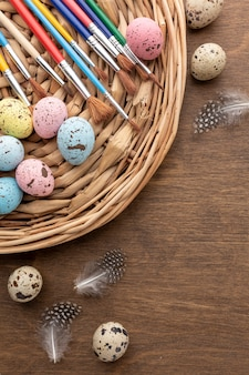 Top view of colorful eggs for easter with copy space and feathers