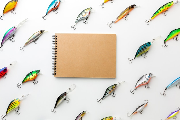 Top view of colorful fish bait with notebook