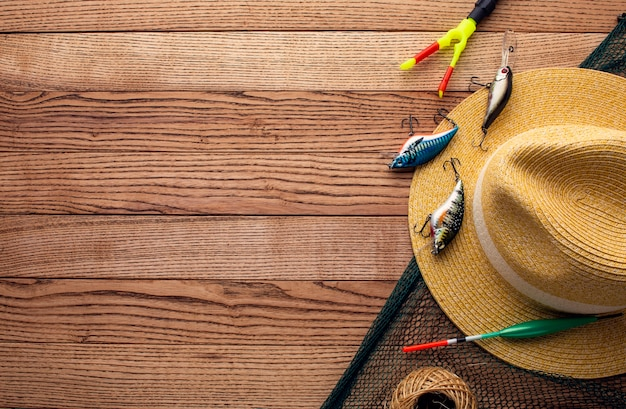 Top view of colorful fishing bait with copy space and hat