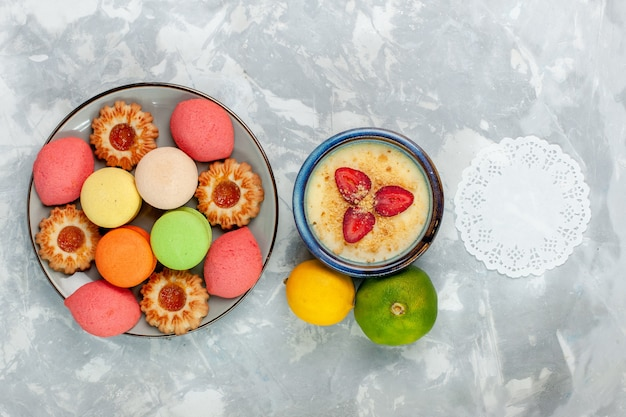 Вид сверху красочные французские макароны вкусные торты с печеньем и десертом на белом столе испечь торт сладкий сахарный десерт бисквит