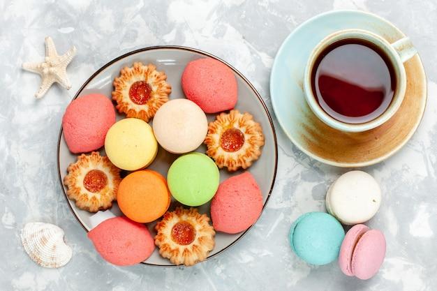Вид сверху красочные французские макароны вкусные торты с печеньем и чаем на белой поверхности испечь торт сладкий сахарный десерт бисквит