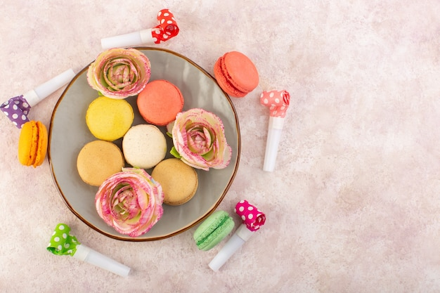 A top view colorful french macarons inside plate on the pink desk sugar cake biscuit