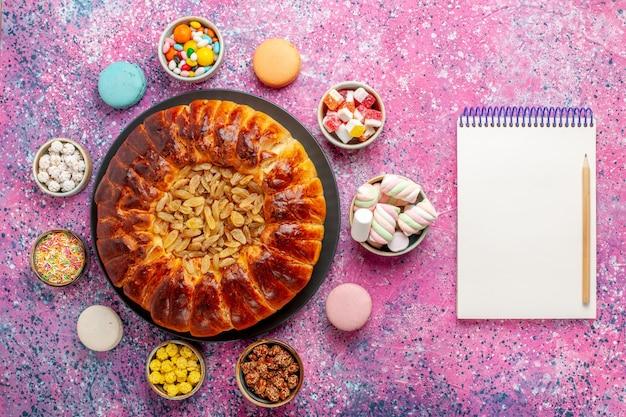 Вид сверху красочные французские макароны маленькие вкусные торты с конфетами и блокнотом на розовом столе сахарная выпечка бисквитное печенье торт пирог