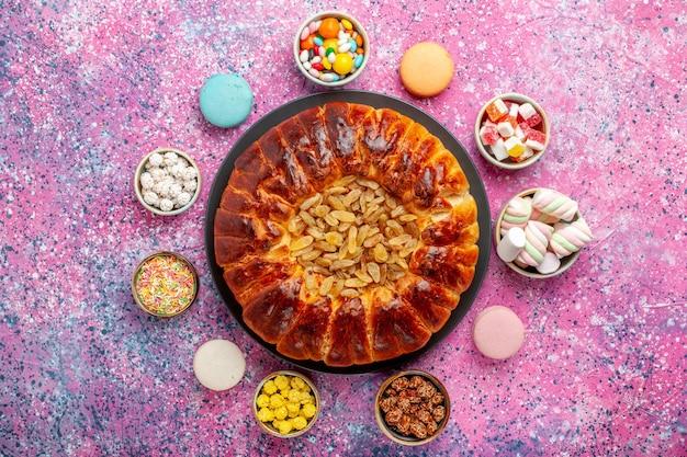 밝은 분홍색 책상에 사탕과 건포도 파이가 달린 상위 뷰 다채로운 프랑스 마카롱 작은 맛있는 케이크 설탕 구워 비스킷 쿠키 케이크 파이 차