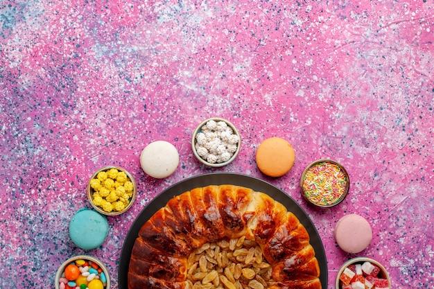 上面図カラフルなフレンチマカロンピンクの机の上にキャンディーとレーズンパイが入った少しおいしいケーキシュガーベイクビスケットクッキーケーキパイ