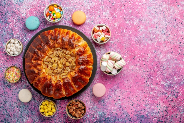 Вид сверху красочные французские макароны маленькие вкусные пирожные с конфетами на розовом столе сахарная выпечка бисквитное печенье торт пирог