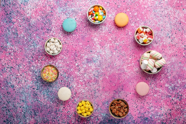 Top view colorful french macarons little delicious cakes with candies on pink desk sugar bake biscuit cookie cake pie