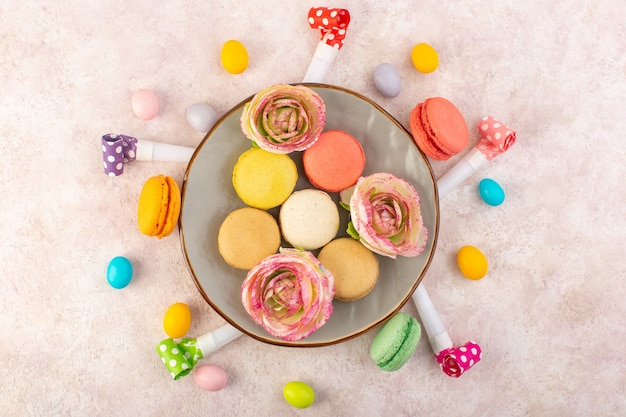 A top view colorful french macarons with candies and flowers on the pink desk cake sweet sugar