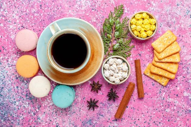 シナモンクラッカーとピンクの机の上のお茶のトップビューカラフルなフレンチマカロンはケーキを焼く甘い砂糖パイの色