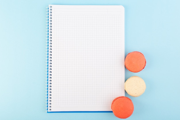 A top view colorful french macarons with copybook on the blue desk cake biscuit sugar sweet