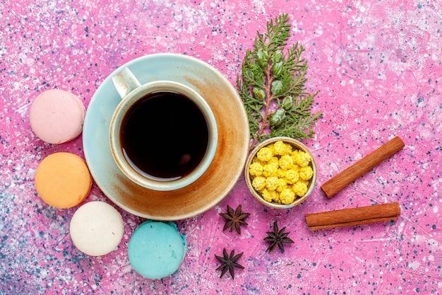 上面図ピンクの机の上にお茶とシナモンのカップとカラフルなフレンチマカロン焼きケーキ甘い砂糖パイの色