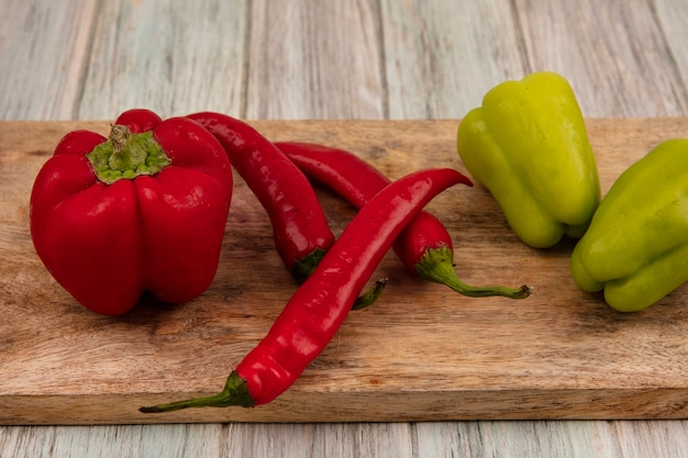 Top view of colorful fresh bell and chili peppers on a wooden kitchen board on a grey wooden background