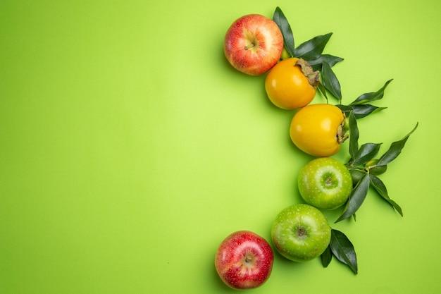 상위 뷰 다채로운 과일 다채로운 사과 감 녹색 테이블에 나뭇잎
