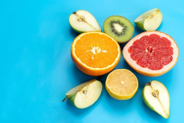 Una composizione di frutti colorati con vista dall'alto ha affettato frutta fresca e fresca sul blu, immagine a colori della frutta