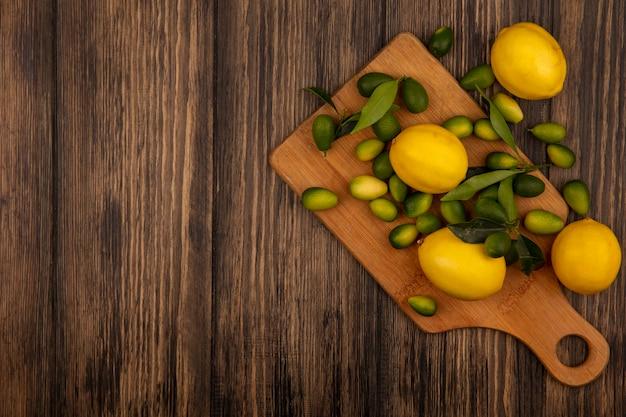 Vista dall'alto di frutti colorati come limoni e kinkan su una tavola da cucina in legno su una superficie in legno con spazio di copia