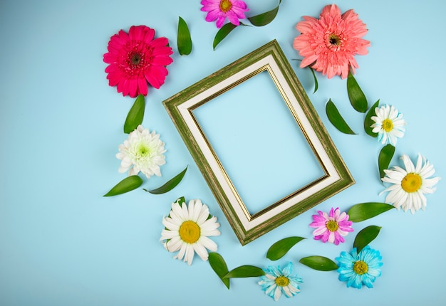 Top view of colorful gerbera flowers with daisy and ruscus leaves arranged around an empty frame on blue background with copy space