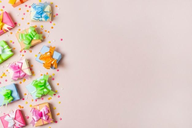 Вид сверху красочные подарки на столе с розовым фоном
