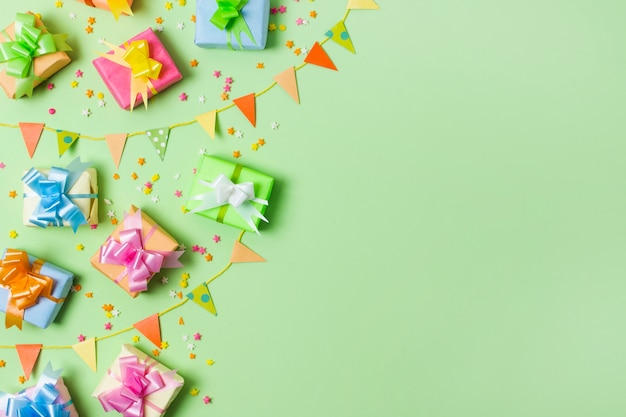 Top view colorful gifts on table with green background