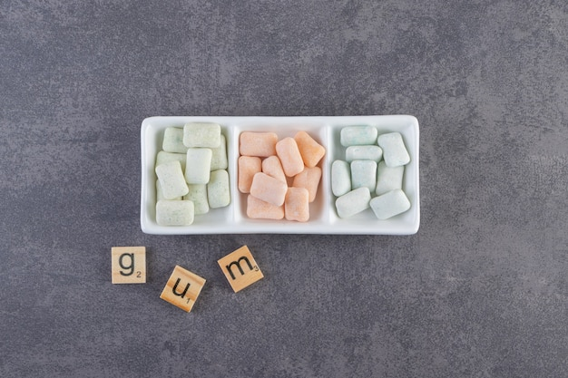 Top view of colorful gums on plate and gum letters on ground.
