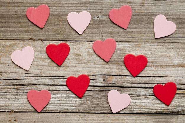 Vista dall'alto di ritagli di cuore colorati su uno sfondo di legno