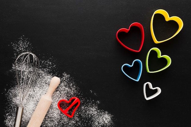 Top view of colorful heart shapes with copy space and rolling pin