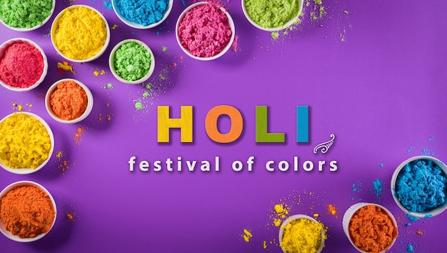Top view of colorful holi powder on purple  background with  text