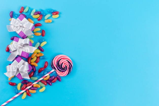 A top view colorful lollipop with little marmalades and purple gift boxes on blue, sugar confectionery candy