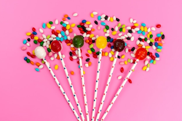 A top view colorful lollipops along with colored candies on pink, color sweet sugar
