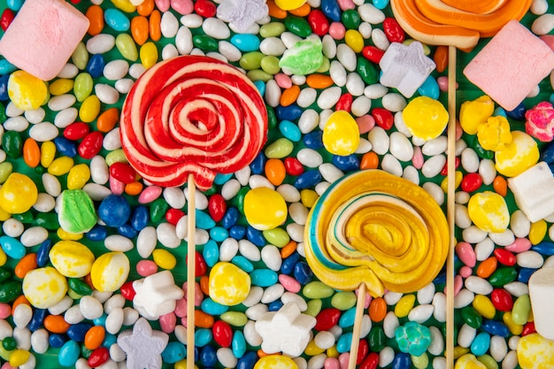 Top view of  colorful lollipops on candies in multi-colored glaze background