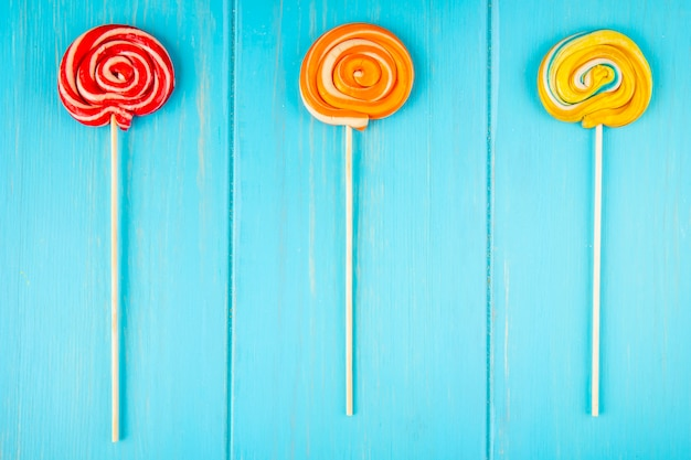 Top view of colorful lollipops on a stick on blue wooden background