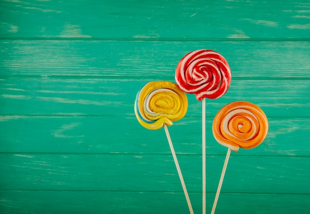 Top view of colorful lollipops on a stick on green wooden background with copy space