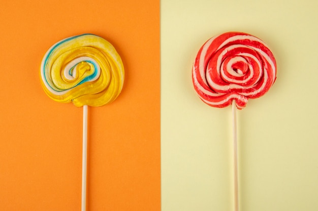 Top view of colorful lollipops on a stick on orange and cream background