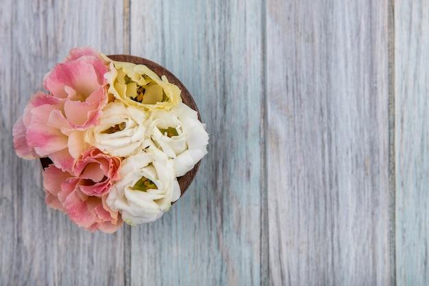 Vista dall'alto di coloratissimi fiori adorabili su una ciotola di legno su un fondo di legno grigio con spazio di copia