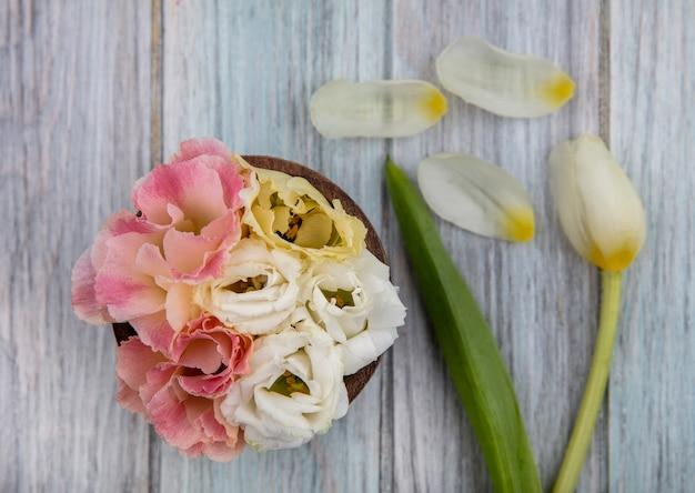 Vista dall'alto di fiori adorabili colorati su una ciotola di legno su un fondo di legno grigio