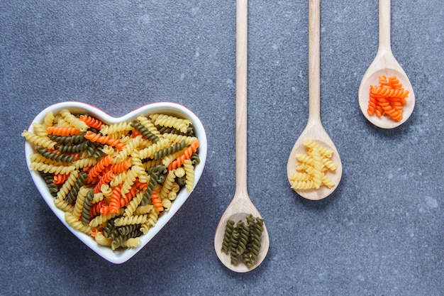 Top view colorful macaroni pasta in heart shaped bowl and spoons on gray surface. horizontal