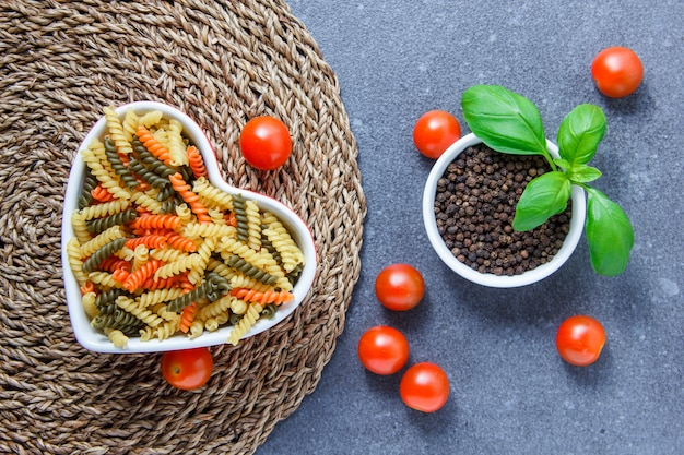 Top view colorful macaroni pasta in heart shaped bowl with tomatoes, black pepper on trivet and gray surface. horizontal