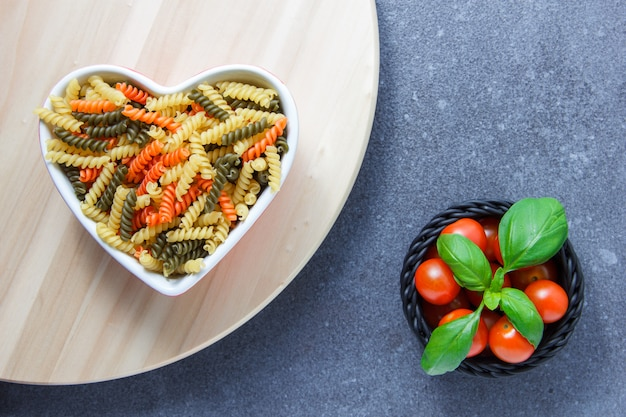 Top view colorful macaroni pasta in heart shaped bowl with tomatoes, leaves, on wooden platform and gray surface. horizontal