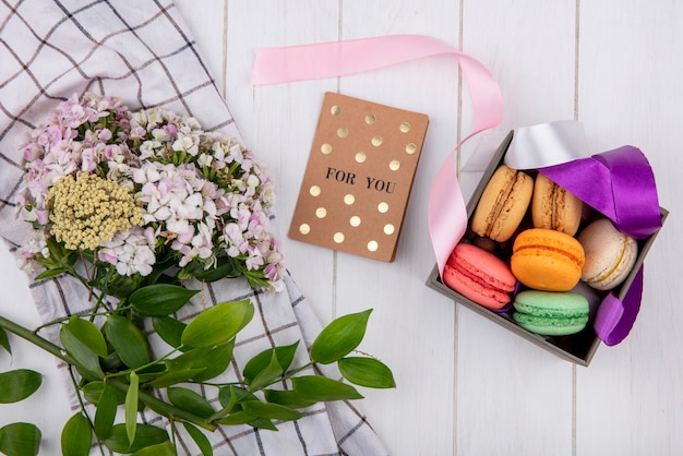 Top view of colorful macarons in a box with colored bows a bouquet of flowers and a postcard on a white surface