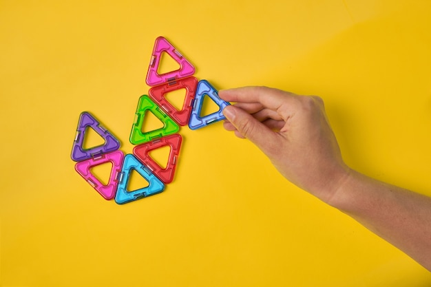 Top view of colorful magnetic building blocks on yellow background