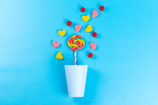 A top view colorful marmalades with lollipops on blue, sweet sugar confectionery