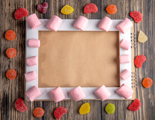 Top view of colorful marshmallow arranged on an empty picture frame and marmalade candies on rustic