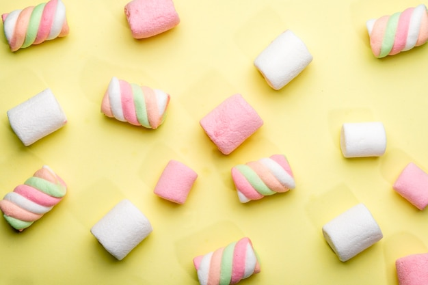 Vista dall'alto di marshmallow colorati sparsi sul giallo